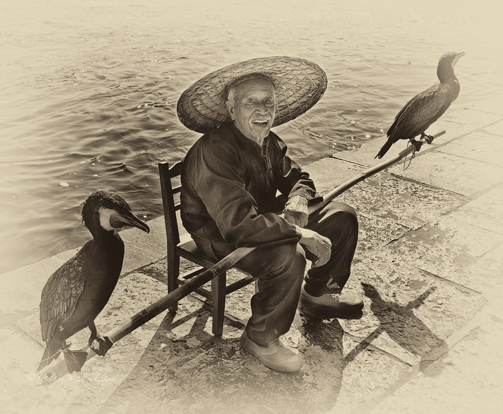 Cormorant fisherman waiting to have his photo taken, Yangshuo landing platform