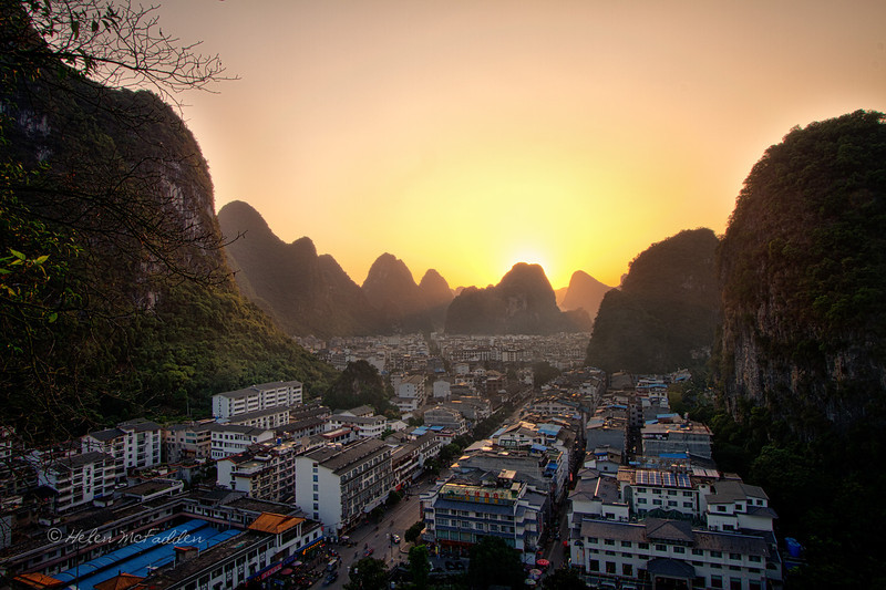 The sun sets amidst the limestone peaks and Yangshuo buildings fill the valley like water