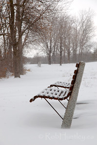 Park bench in winter along the Ottawa River Parkway.