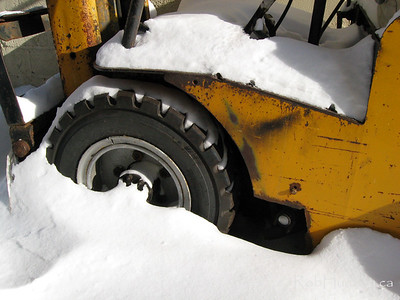 Fork lift with wheels buried in snow.