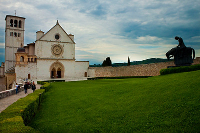 The Basilica di San Francesco (Basilica of St. Francis) with a statue of St. Francis on a horse in front, Assisi, Italy 2010