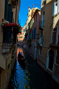 A gondolier navigates one of the narrow canals of Venice, Italy 2010