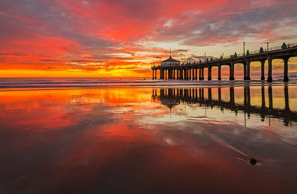 Manhattan beach pier sunset reflected in low tide