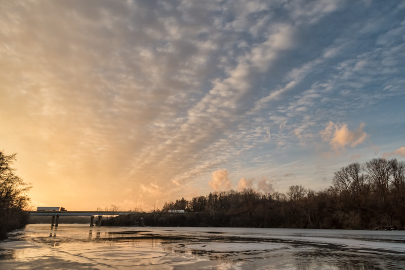 Cloud trails at sunset over a partly frozen Huron River