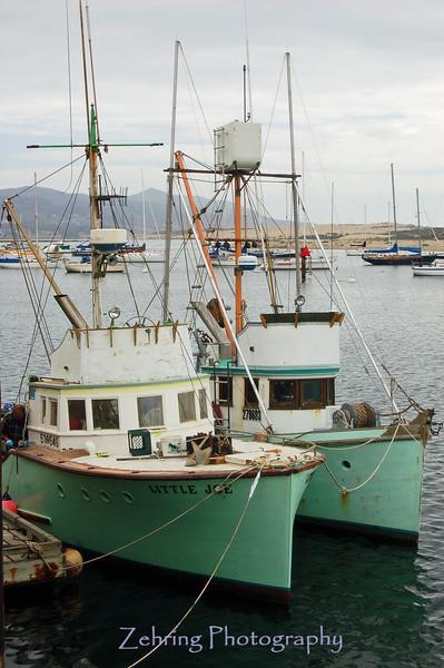 Fishing boats moored at the harbor inlet at Morro Bay, CA.
