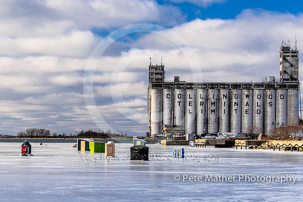 Fish huts and the Collingwood Grain Terminal in January or Febrary on a beatiful day wiyh puffy white clouds with wintery sunset and very cold. This is located in Collingwood, Ontario on Georgian Bay.