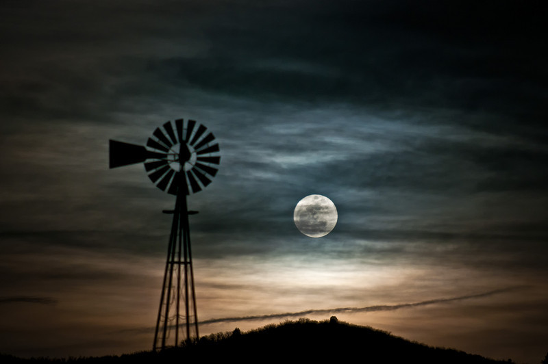 A Springtime full moon rising over open colorado farmland.