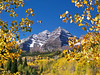 Changing aspens frame a view of the Maroon Bells in Autumn, Colorado Elk Range.
