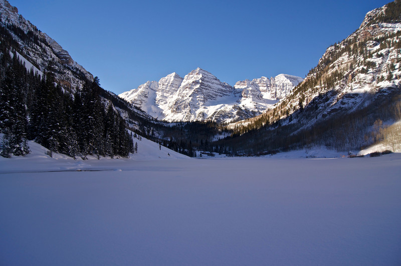 This famous scene is typically crowded with tourists, however in the winter, when the road is closed, Maroon Lake becomes a place of frigid solitude; Colorado Elk Range.