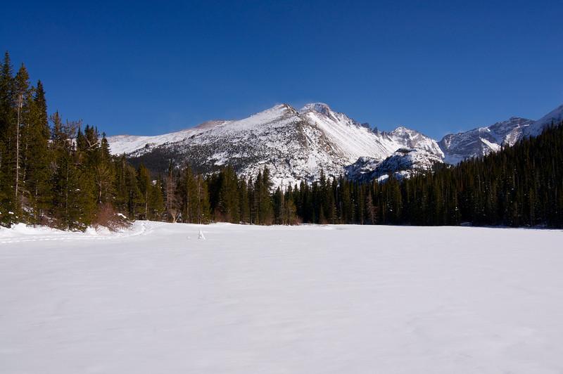Longs Peak rises over frozen Bear Lake in early spring; Rocky Mountain National Park, Colorado.