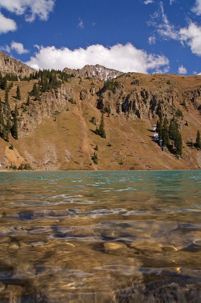 """The crystal clear water of """"lower"""" Blue Lake, reflecting its characteristic turquoise in the distance, lies nearly 3000 feet below the summit of Mt. Sneffels; Colorado San Juan Mountains."""