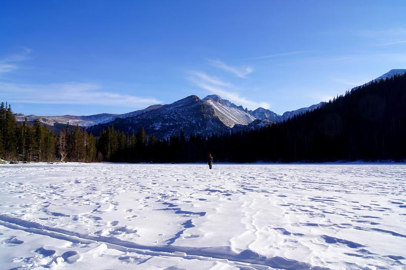 Admiring Longs Peak while taking a stroll across frozen Bear Lake in December; Rocky Mountain National Park, Colorado.