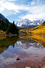 Early afternoon storm lifts, revealing the Maroon Bells' reflection on the clear waters of Maroon Lake through soft, cloud-filtered light.
