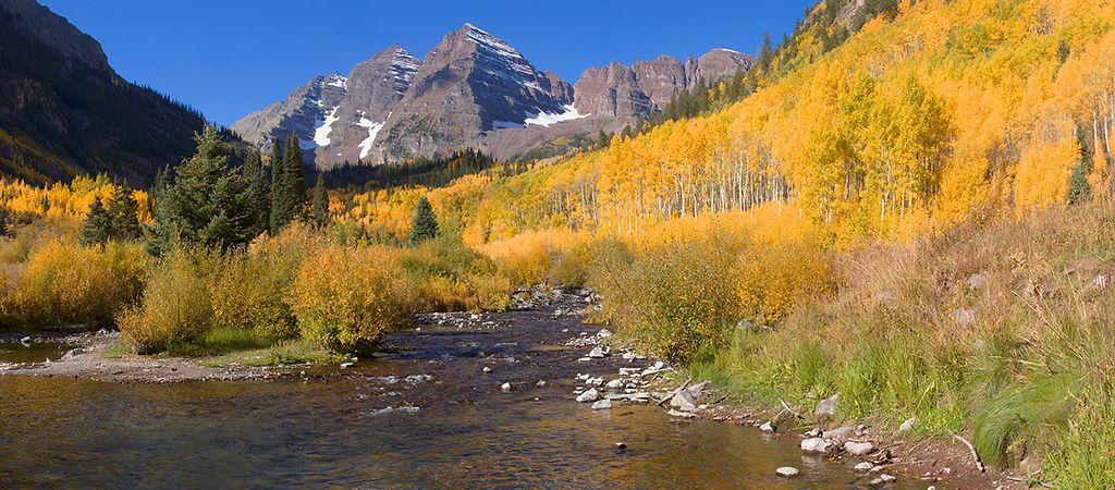 (Maroon Bells Pano-1)  Maroon Creek meanders toward Maroon Lake as the Maroon Bells tower above on a gorgeous autumn day.