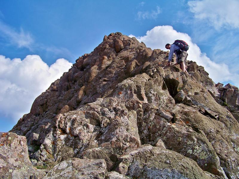 Climbing an exposed ridge just below the summit of Mt. Sneffels (14,150 ft.); Colorado San Juan Range.