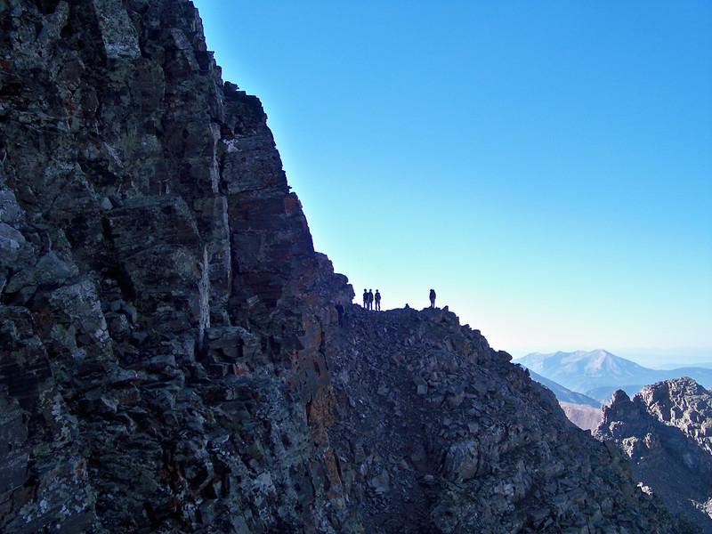 Hikers traverse ledges below the Maroon Peak south ridge, Colorado Elk Range