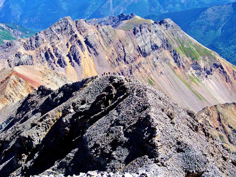 A line of hikers rope up on the ridge crest below the Castle Peak summit, Colorado Elk Range.