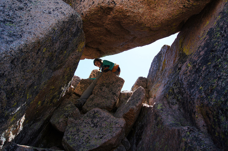 A hiker squeezes through a narrow gap leading to the Sunlight summit; Colorado San Juans.