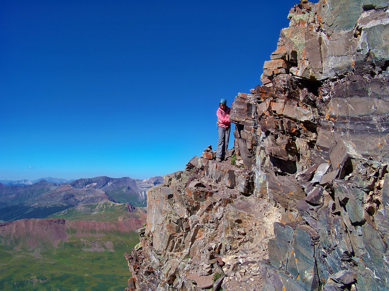 A climber negotiates one of many cliff ledges below the Maroon Peak south ridge