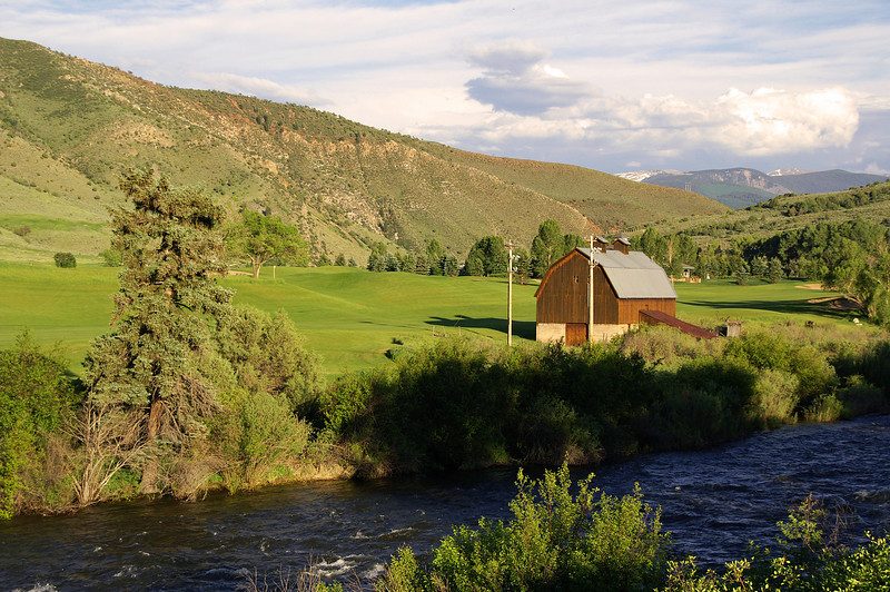 The Eagle River rushes by the barn and golf course at Wolcott, CO