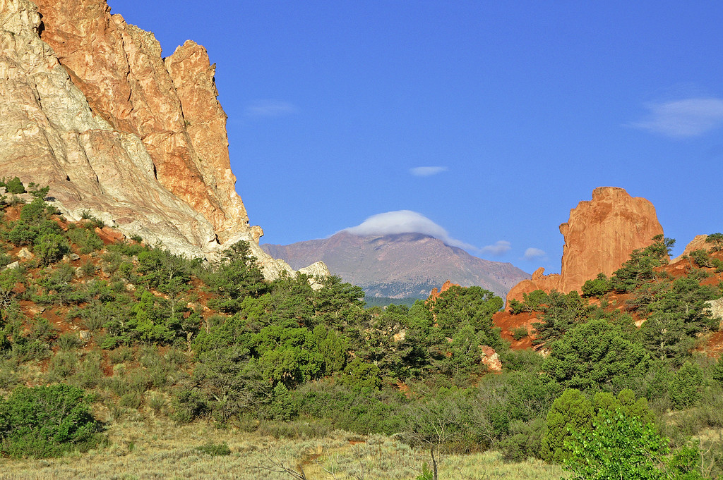 Pikes Peak is shrouded in a shape matching cloud as seen through the colorful formations of Garden of the Gods.