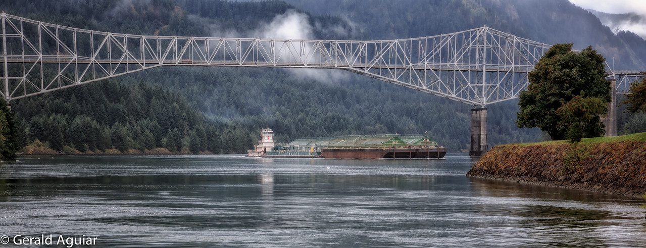 A barge going beneath the Bridge of the Gods on the Columbia River in Cascade Locks, Oregon.