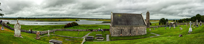 Clonmacnoise, or Cluain Mhic Nóis<br /> Panorama that incudes the steps leading up to O'Rourke's Tower (left), Temple Connor (center), the tower attached to the ruins of Temple Finian (to the immediate right of Temple Corror), and the modern shelter termed 'Mass Shelter' on the map (right).<br /> <br /> The small boat dock on the River Shannon can be seen along the left, also.  Numerous grave markers and carved crosses and headstones of a wide range of dates are also visible.  The more modern cenemtery that is outside the grounds of the historic religious site can be seen on the far right.<br /> <br /> Taken August 17, 2007<br /> Ireland
