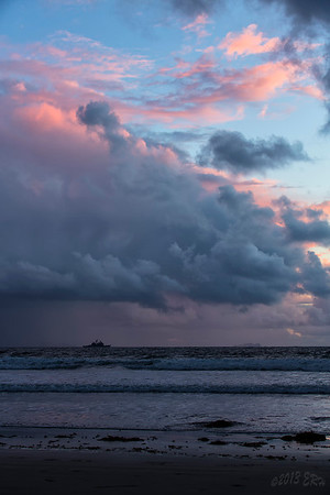 So close, yet so far.  A Ticonderoga class cruiser sitting off the coast during a stormy Friday afternoon sunset.