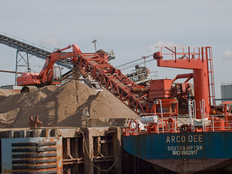 Arco Dee unloading at the wharf. The conveyor belt discharge system. Copyright Peter Drury 2010<br /> The hopper on the jig feeds this discharge system. Note the tracked scoop moving the discharged material to the the land based hopper.