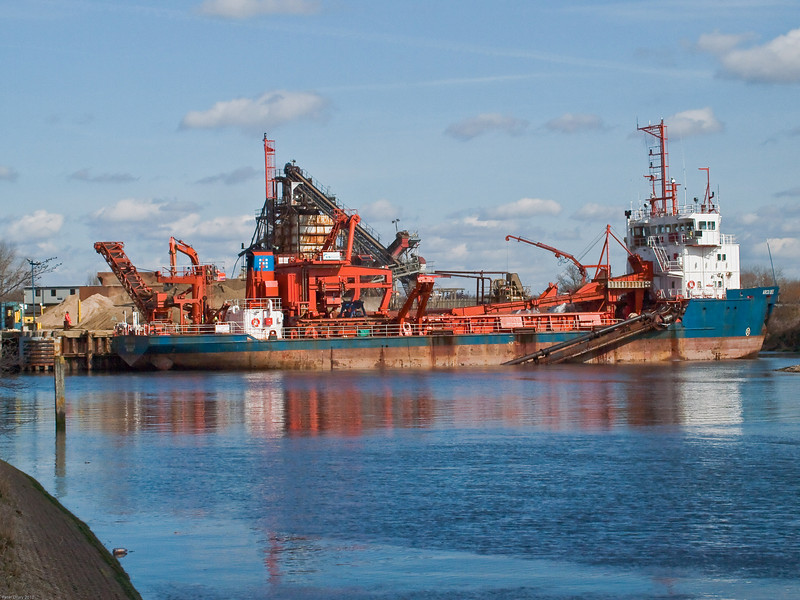 Arco Dee unloading at the wharf. Copyright Peter Drury 2010<br /> Unloading now completed, one end of the black pipes is lowered into the sea and water is pumped into the hold to clean it.