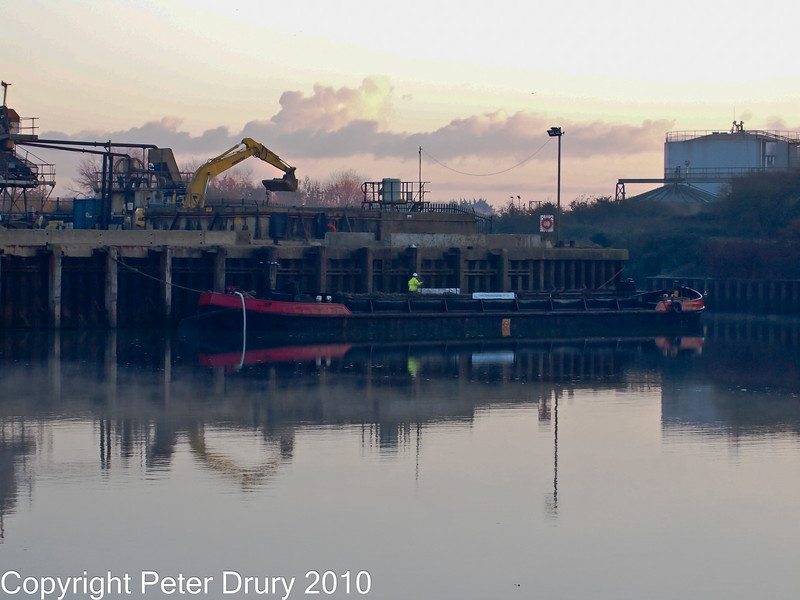 16 Nov 2010 - Dawn loading at Aggregates Wharf, Langstone Harbour. Copyright Peter Drury 2010.<br /> The barge was loaded before dawn by the mechanical shovel. The seamen are preparing the barge to be moved out by the tug.<br /> E5 + Sigma 50-500, ISO 1600, f7.1, Aperture Priority