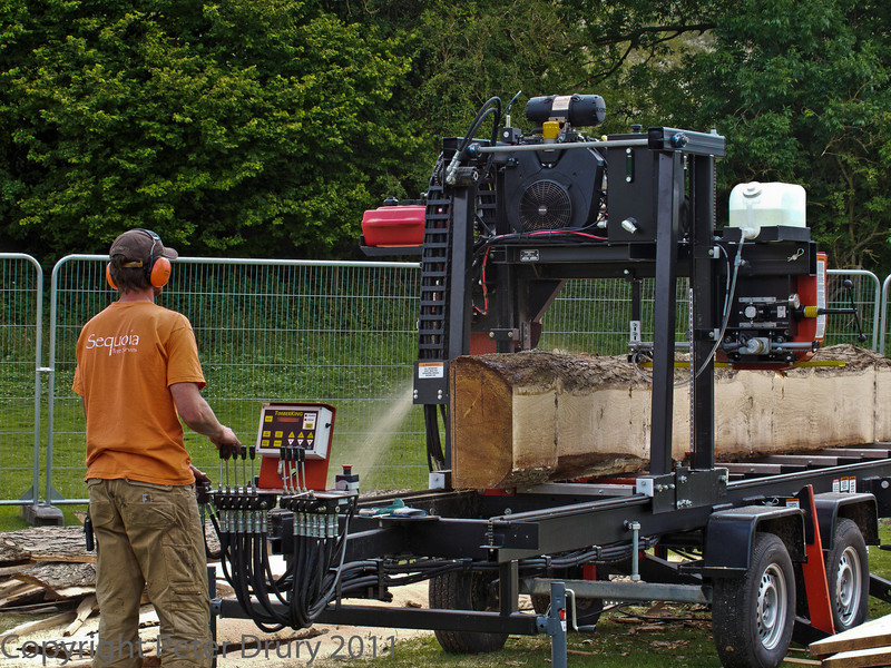 10 July 2011 Woodcraft fair 2011. Mobile saw mill in action.<br /> Ideal to take into the forest and cut the timber without the additional eonomic and environmental costs of trucking the tree trunks to the saw mill. The saw dust and bark become ideal habitats for invertebrates which provide an additional souce of food for the birds etc. Over time, the rotting timber returns nutrients etc to the soil. A win win.