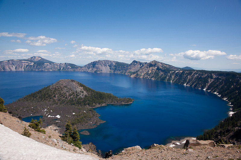 Crater Lake and Wizard Island, in Cater Lake National Park, Oregon.  The lake is the deepest in North America, having formed after the massive eruption and subsequent collapse of Mount Mazama, about 7600 years ago.  Wizard island is a lava dome that subsequently formed inside the crater.  There are no known river flows in or out of the lake, so it is fed by rainwater and drained through evaporation.  The deep blue colour is a result of the lake's extreme depth.