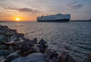 A cargo ship, with the sunset at its stern, heads down the St. Johns River and out to sea.