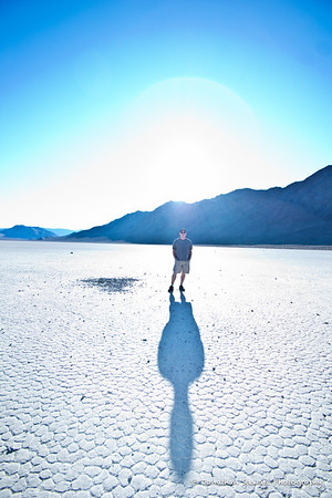 Ryan backlit on the playa, showing the typical hexagonal mud crack saucers.