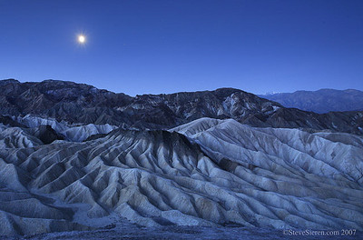 Formations and Moon at Zabriskie Point with Bennett Peak in the distance.  Death Valley National Park at dawn.