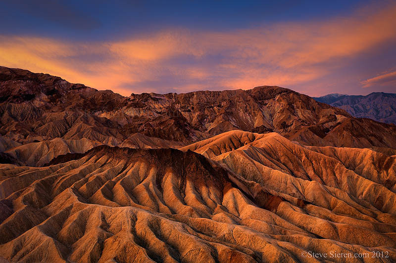 View of the badland formations at Zabriskie Point in Death Valley underneath a very colorful canopy of clouds.
