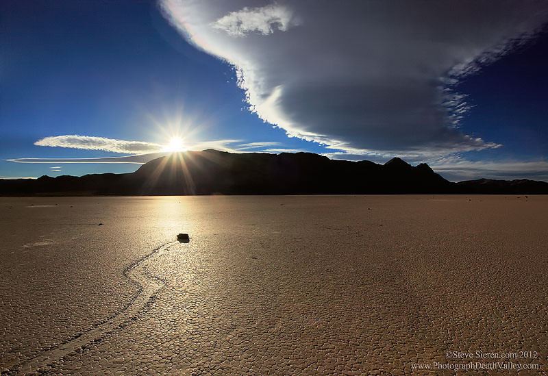 The sun sets below a lenticular cloud on the moving rock racetrack playa in Death Valley National Park.
