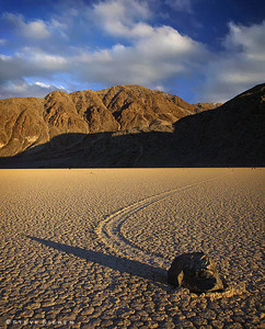 The Race Track - Death Valley  Tucked in a remote valley between the Cottonwood (Panamint Range) and Last Chance Ranges, the Racetrack is a place of remarkable beauty and mystery. The Racetrack is a playa dry lakebed, best known for it's strange moving rocks. Although no one has actually seen the rocks move, the long meandering tracks left behind in the mud surface of the playa attest to their activity.  Wind is one of the factors in the mystery of the moving rocks.