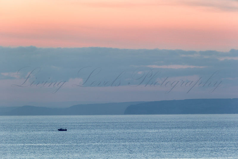 Dusk over the calm English Channel near Burton Bradstock, on an early winter's day as a fishing boat heads back along the coast.