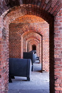 Arches and Cannons of Fort Zachary Taylor State Park.  The repeating arches seeming go on forever and the cannons are evenly spaced between.