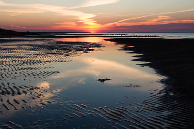 The sun goes down on low tide at Aboiteau beach, New Brunswick. This Acadian part of the country has great seafood and an entirely different french canadian culture than Quebec. This area is minutes away from famous Shediac Bay
