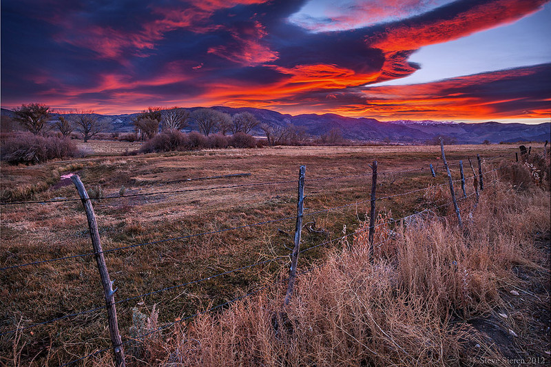 Barbed wire fence under lenticular clouds near Walker, California.