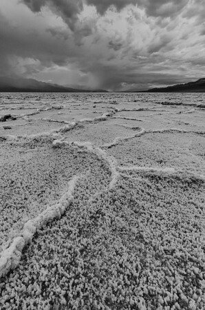 A storm blew across the valley floor at Badwater Basin, 282 feet below sea level. When it does rain, water evaporates rapidly, leaving salt deposits that form into these weird ribs in honeycomb shapes.