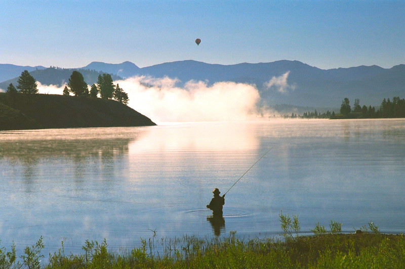 Hot air ballon at dawn and fisherman, Tahoe National Forest