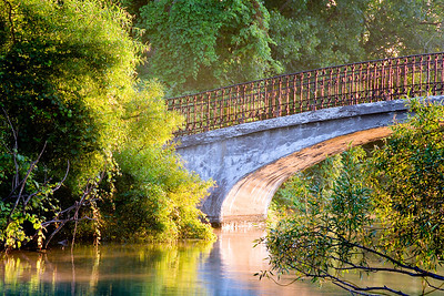 "#59 The early morning light through the canal around the 1st bridge is always something to see in the summer. Depending on the humidity and the clouds in the morning sky, the sun paints the trees, bushes, water and bridge with some of the most amazing light you'll ever see.  The 1st of the 3 bridges.  *For information on purchasing prints and canvas gallery wraps, click the ""Purchasing"" tab at the top of the page. If viewing on your mobile device, scroll to the bottom of the page and click the ""Full Site"" tab to view as if you were on your home PC and then go to the ""Purchase"" tab to for purchasing info. In mobile mode, you will not see the standard navigation bar with the ""Purchase"" tab."