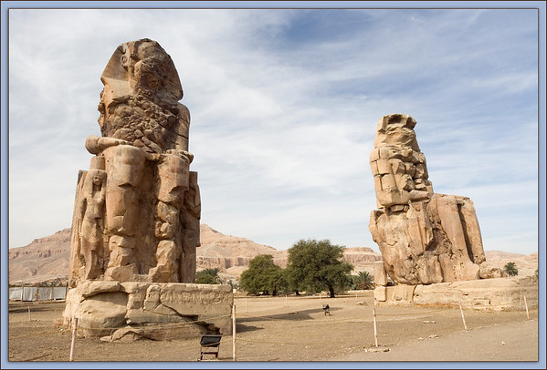 "Colossi of Memnon:<br /> The two figures of Amenhotep III are in a seated position with the hands resting on his knees. The forms look to the east and thus the rising sun.  ""Memnon"" means Ruler of  the Dawn. The two small figures next to the legs represent Amenhotep's wife ,Tiy , and his mother Mutemwiya."