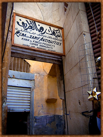Reba el Zarif Antiquities Sign in the maze of alleyways at the Kahn el Khalili advertises copper handcrafts with Arabic and Pharonic Designs.