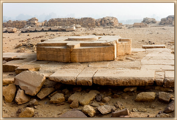 """""""Joy of Ra""""...Niuserre's temple of the solar cult in Abu Gurab..features this lovely alabaster altar in the center of the courtyard east of what was once a magnificent obelisk (base of which is seen in other pics in this series.) The altar is constructed of five large blocks of alabaster arranged with a central disc surrounded by four carved sections representing the hierogliphic sign Htp(hotep=offering). The symbol can be translated """"May Ra be satisfied.""""<br /> <br /> We visited this site on a soft hazy morning;it was accessible by hiking through the lush grove of mango trees and date palms of a small village at the edge of the desert. The place is very serene and conducive to imagining what ceremonies might have been like on these grounds so long ago....Abu Gurab, Egypt"""