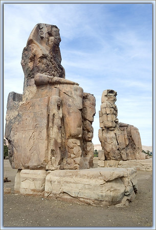 The Colossi of Memnon are twin stone statues of Pharaoh Amenhotep III. They are made from blocks of quartzite sandstone thought to have been quarried near Cairo or north of Aswan. Located in Thebes for the past 3400 years, they sit  cross the Nile from Luxor. The two figures stand about 60 ft in height including the platforms upon which they sit.